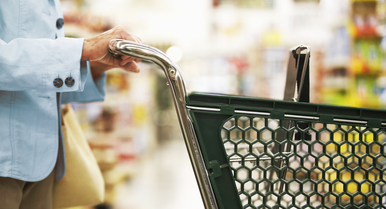 Woman Pushing Shopping Cart --- Image by © Royalty-Free/Corbis